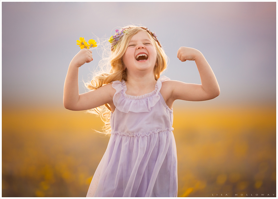 Adorable little girl with blonde hair, a purple dress, and purple flower crown poses for outdoor portraits in a field of yellow wildflowers near Las Vegas.  LJHolloway Photography is a Las Vegas Child Photographer.