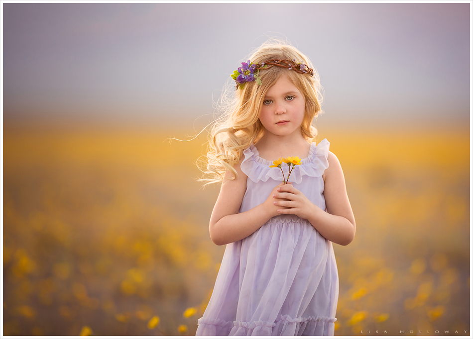 Adorable little girl with blonde hair a purple dress and purple flower crown poses