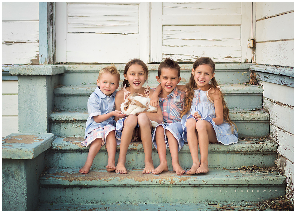 4 cute children wearing the chambray and peach Well Dressed Wolf boutique clothing sit on stairs with mint green peeling paint. LJHolloway Photography is a Las Vegas Child Photographer.