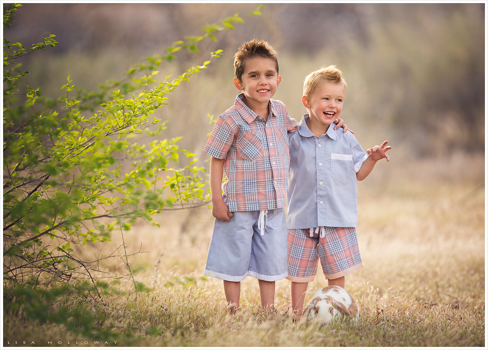 2 cute little boys wearing the chambray and peach Well Dressed Wolf outfits stand outside in the golden grass with their pet bunny. LJHolloway Photography is a Las Vegas Child Photographer.