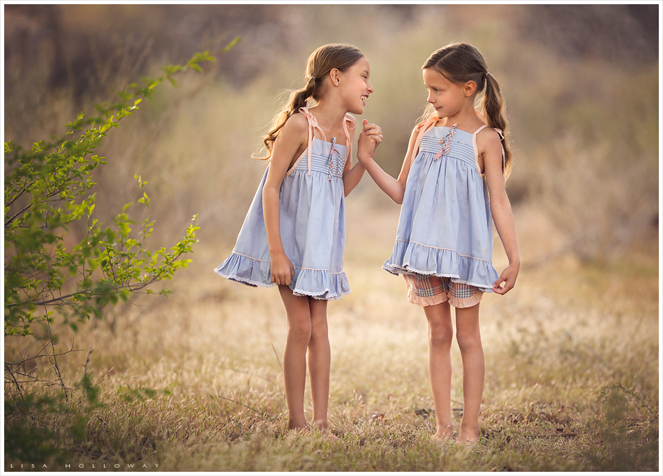 2 cute little girls wearing the chambray and peach Well Dressed Wolf dresses stand outside in the golden grass. LJHolloway Photography is a Las Vegas Child Photographer.
