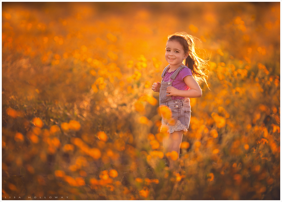 A cute little girl with a ponytail plays in a field of yellow wildflowers at sunset. LJHolloway Photography is a Las Vegas Child Photographer.