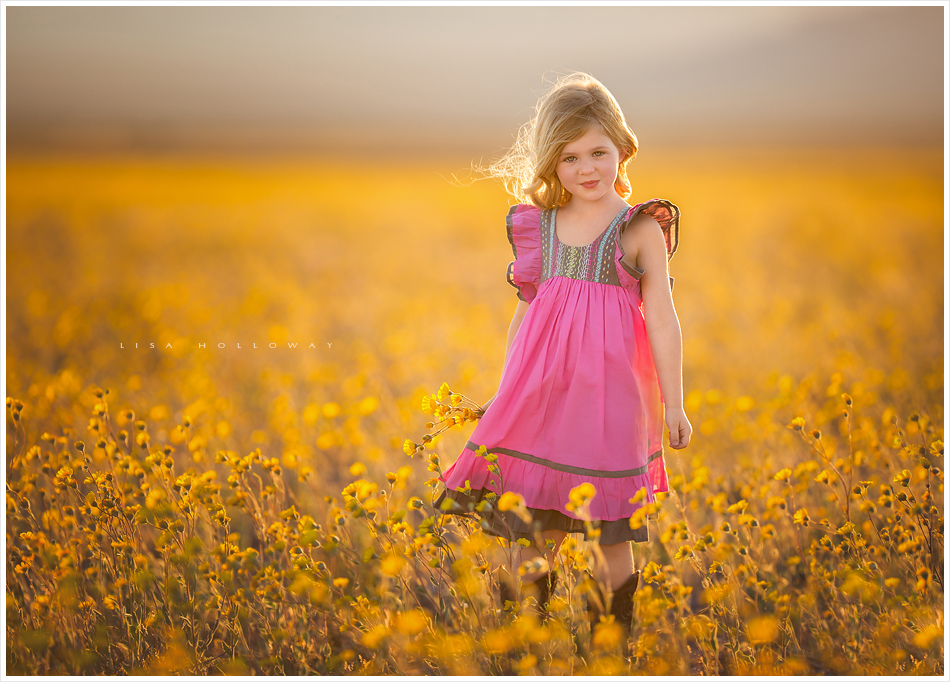 Adorable little girl with blonde hair and a pink dress poses for outdoor portraits in a field of yellow wildflowers near Las Vegas. LJHolloway Photography is a Las Vegas Children