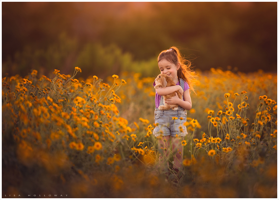 A cute little girl holds a pet bunny in a field of yellow wildflowers outdoors for a portrait. LJHolloway Photography is a Las Vegas Child Photographer.