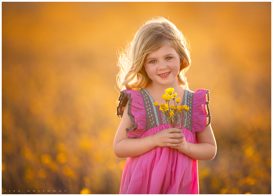 Adorable little girl with blonde hair and a pink dress poses for outdoor portraits in a