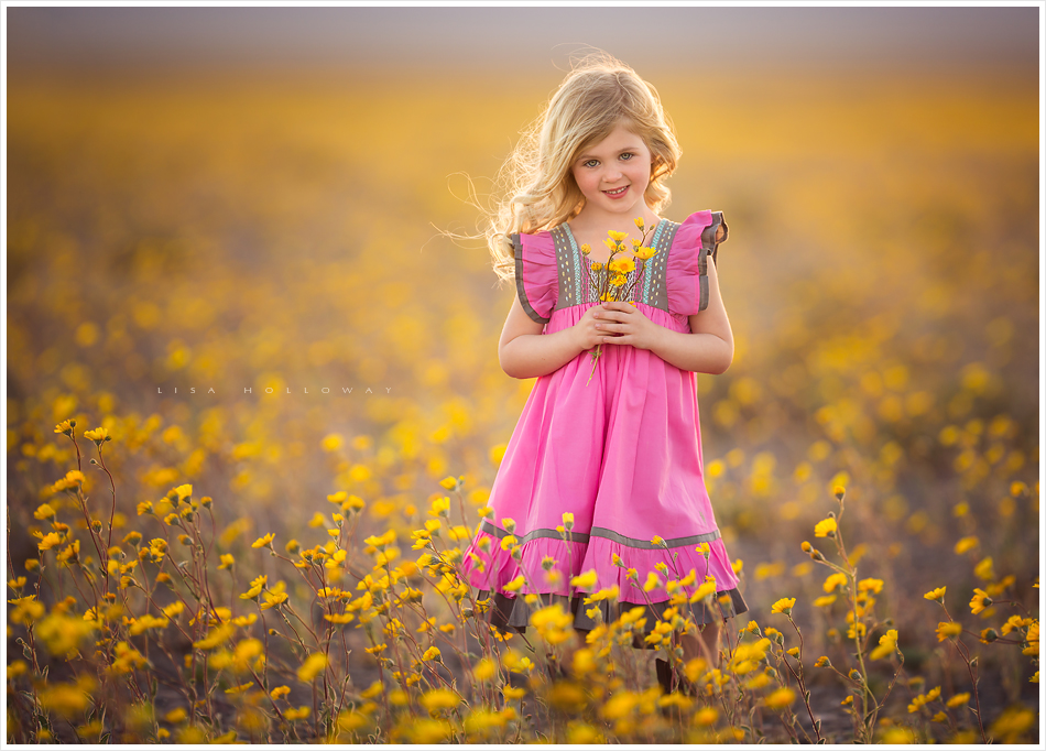 Adorable little girl with blonde hair and a pink dress poses for outdoor portraits in a field of yellow wildflowers near Las Vegas. LJHolloway Photography is a Las Vegas Children's Photographer.