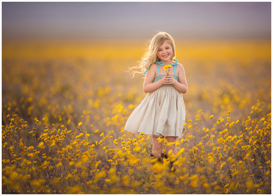 Adorable little girl with blonde hair and a tan and blue dress poses for outdoor portraits in a field of yellow wildflowers near Las Vegas. LJHolloway Photography is a Las Vegas Children's Photographer.