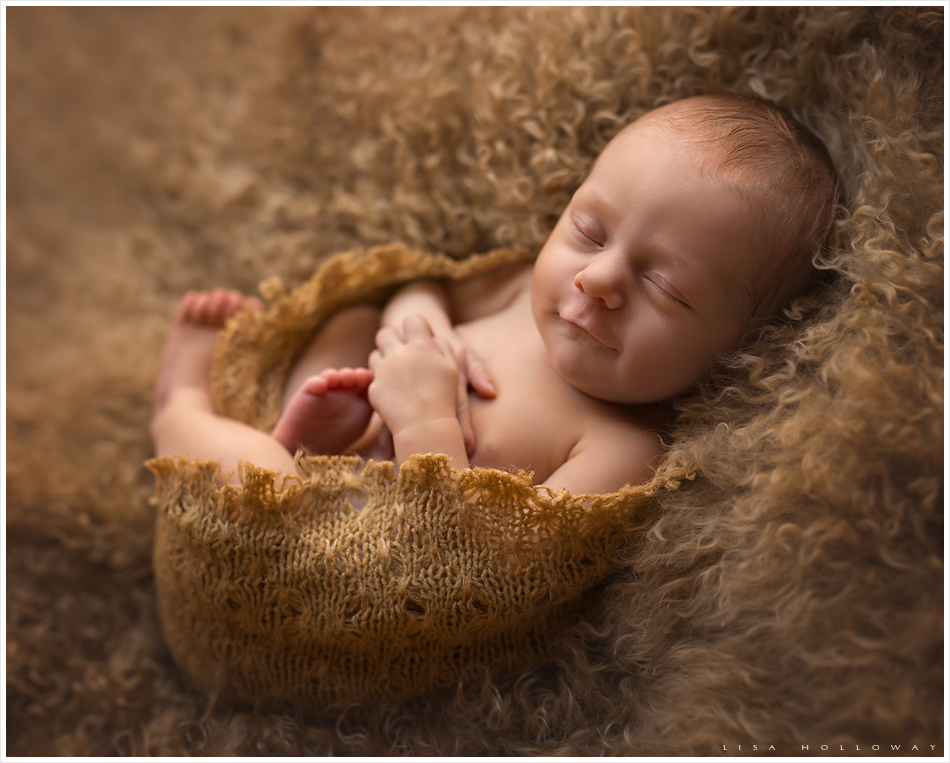 Adorable newborn baby girl sleeps on her tummy on a cream colored blanket. LJHolloway Photography is a Las Vegas Newborn Photographer.