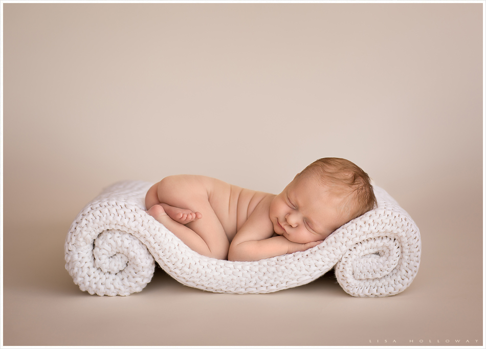 Cute newborn baby girl sleeps on her belly on a rolled up white knit blanket and