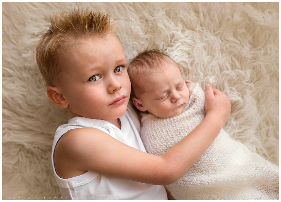 Little boy poses for a portrait with his new baby sister. LJHolloway Photography is a Las Vegas Newborn Photographer.
