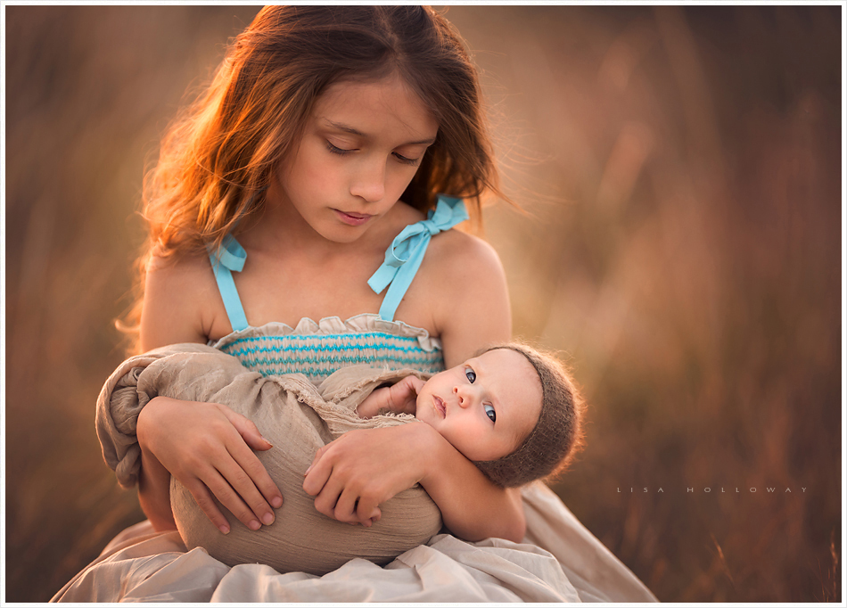 Young girl poses for a portrait with her new baby sister ljholloway photography is a