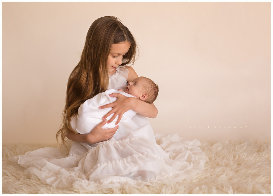 Young girl poses for a portrait with her new baby sister. LJHolloway Photography is a Las Vegas Newborn Photographer.