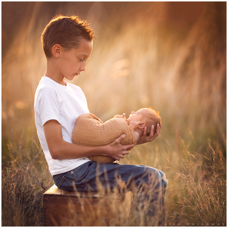 Young boy poses for a portrait with his new baby sister. LJHolloway Photography is a Las Vegas Newborn Photographer.
