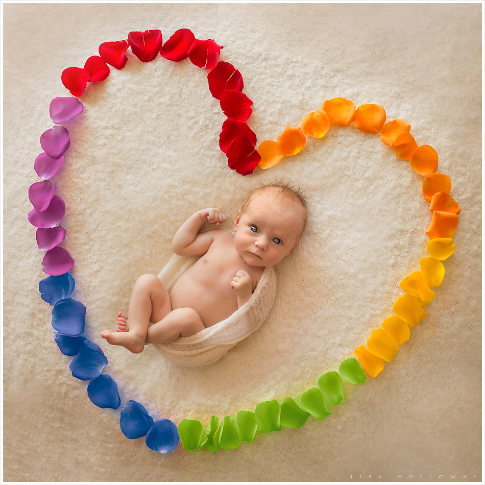 Beautiful rainbow baby portrait of a newborn baby girl surrounded by rainbow colored rose petals symbolzing