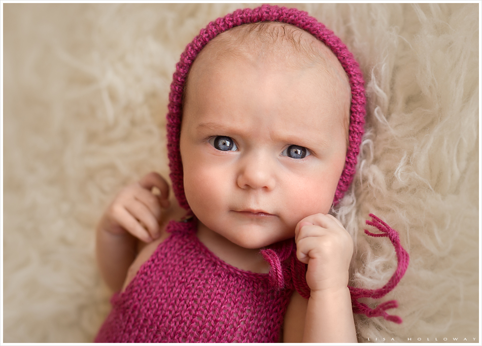 Adorable newborn baby girl with blue eyes wears a pink knit outfit and hat and grins for a portrait. LJHolloway Photography is a Las Vegas Baby Photographer.